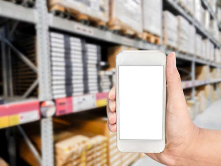 Hand holding mobile smart phone on shelf in Warehouse blurred Background