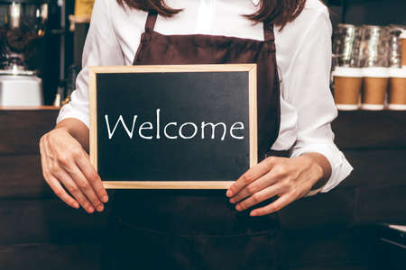 Photo for Barista holding chalkboard with word WELCOME in coffee shop restaurant - Royalty Free Image