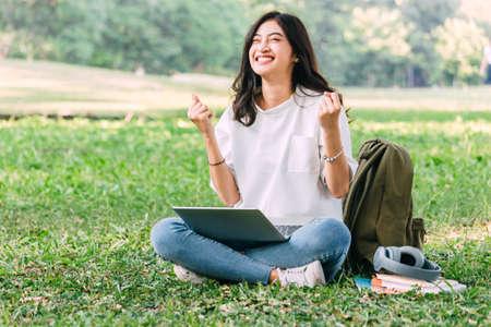 Foto de Woman relax and use a laptop computer sitting on grass in park - Imagen libre de derechos