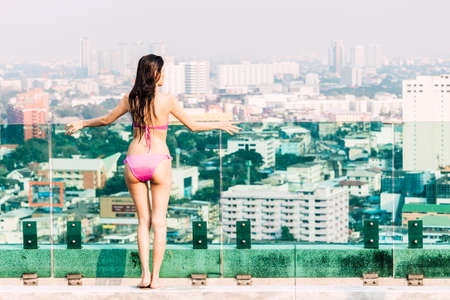 Woman wearing two piece bikini in summer vacation relaxing on city background