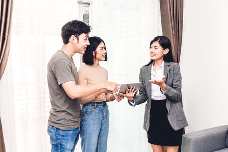 Foto de Real estate agent holding tablet and talk with young couple in a house for sale. business and real estate concept - Imagen libre de derechos