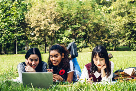 Photo pour Group of smiling international students or teenagers sitting and using laptop computer doing their homework with book together in park at university.Education and friendship Concept - image libre de droit