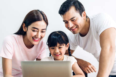Photo for Happy family father and mother with daughter sitting and looking at laptop computer together in the living room at home - Royalty Free Image