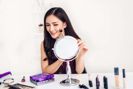 Photo pour Smiling young beautiful asian woman fresh healthy skin looking on mirror and holding make-up brushes with cosmetics set at home.facial beauty and cosmetic concept - image libre de droit