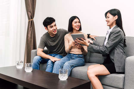 Photo pour Real estate agent holding document and talk with young couple in a house for sale. business and real estate concept - image libre de droit