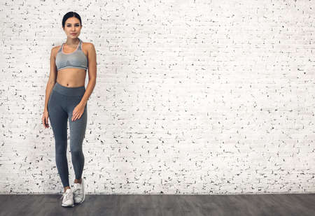 Foto per Sport woman in sportswear relax stand after workout against copy space for adding text with white wall background.Diet concept.Fitness and healthy lifestyle - Immagine Royalty Free