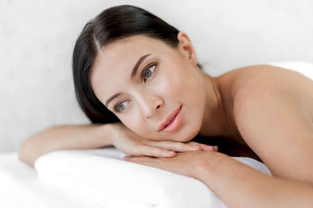 Photo for Beautiful young woman beauty skin treatment relaxing lying on towel in massaging and spa salon - Royalty Free Image
