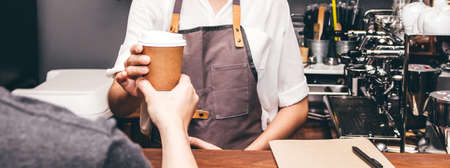 Photo pour Woman barista giving coffee cup to customer at cafe - image libre de droit