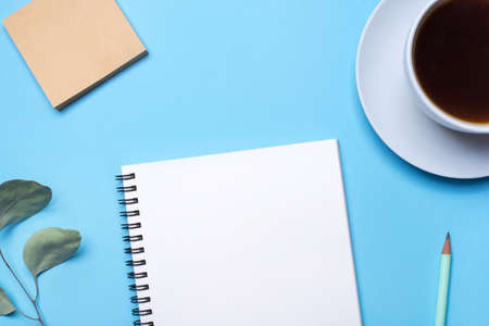 Photo pour Blue background with notepad, pencil and cup of coffee. Top view with copy space, flat lay. - image libre de droit