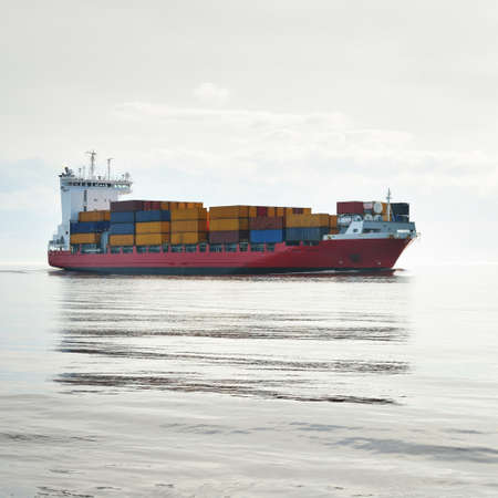 Photo pour Large cargo container ship sailing in a still sea water on a clear day. Panoramic view. Freight transportation, global communications, logistics, industry, business, economy, environmental damage - image libre de droit