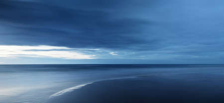 Baltic sea at sunset. Dramatic twilight sky, blue glowing clouds. Waves, splashing water. Picturesque scenery, seascape, cloudscape, nature. Panoramic view, long exposure