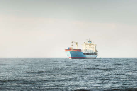 Photo pour Large blue cargo container ship with a crane sailing in an open sea. USA. Freight transportation, nautical vessel, global communications, logistics, shipping, delivery, industry, commerce, economy - image libre de droit
