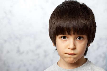 close-up portraits of thoughtful boy bit his li