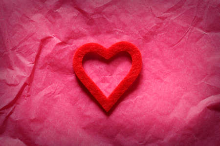 Red heart on pink paper.From above