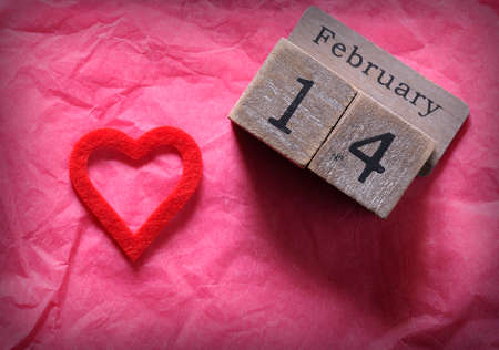 Wooden calendar with February 14th and red cut heart on pink paper. From above.