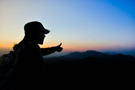 Photo pour silhouette woman traveler see view sunset on the mountain in moment of happiness.feel relax lifestyle. - image libre de droit