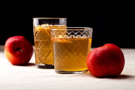 Foto de Two vintage glasses with apple cider on black background. Christmas beverages concept. Two red apples and rosemary sprig aside.  Warm backlight. Horizontal composition. Side view. - Imagen libre de derechos