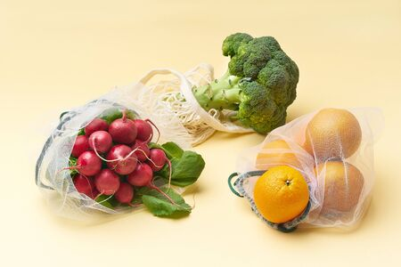 Foto für Zero waste food shopping with reusable bags. Flat lay with fruits and vegetables in textile packaging. Broccoli, radishes and oranges on yellow background. - Lizenzfreies Bild