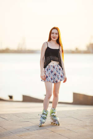 red-haired woman in roller skate in a city park on her T-shirt and bright blue chert in the park grow spruce lined road pavement
