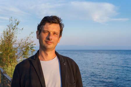 Foto de Portrait of a middle aged man in the summer at sunset on the shore of lake Baikal - Imagen libre de derechos