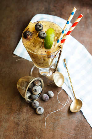Blueberry and melon smoothie in a glass with a straws with mint and lime over vintage wooden table with fresh berries and melon.