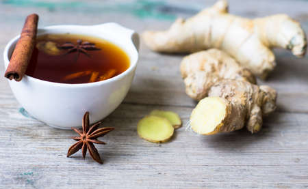 Cup of tea with ginger, cinnamon sticks and anise star spice on the rustic background