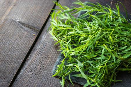 Tarragon herb as a organic salad ingredient on dark wooden table