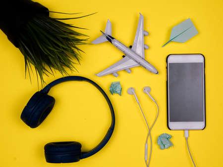 Photo pour Smartphone, headphones, plane toy, green pot plant and paper planes - image libre de droit