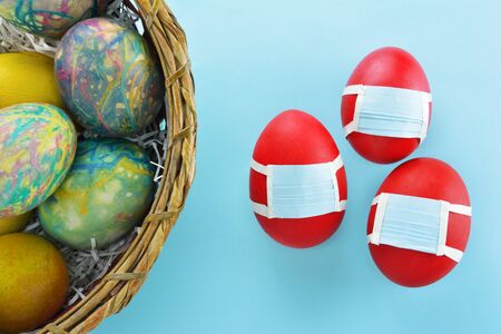 Photo for Basket with colorful eggs and  red eggs with protection masks beside on light blue background - Royalty Free Image