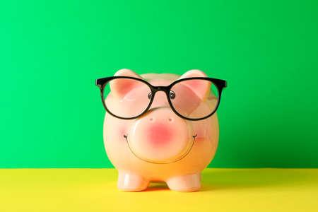 Foto de Happy piggy bank with glasses on color table against green background, space for text. Finance, saving money - Imagen libre de derechos