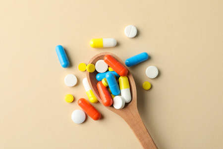 Photo pour Spoon and pills on beige background, space for text - image libre de droit