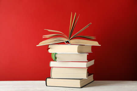Photo for Stack of books against red background, space for text - Royalty Free Image