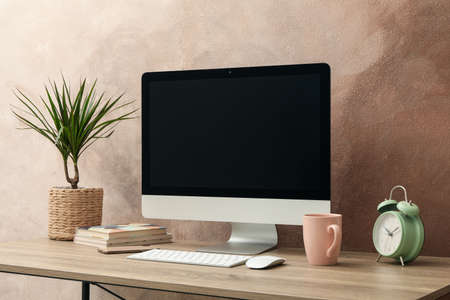 Photo pour Workplace with computer and plant on wooden table. Light brown background - image libre de droit