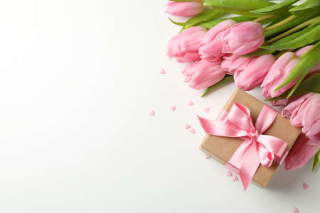 Photo for Tulips, gift and hearts on white background, space for text - Royalty Free Image