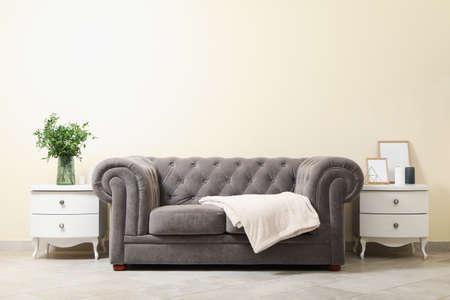 Foto de Cozy interior with sofa against light beige wall - Imagen libre de derechos