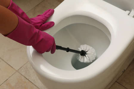 Photo for Woman in rubber pink gloves cleans toilet bowl with brush - Royalty Free Image