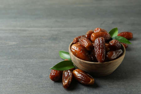 Photo for Bowl of dried dates on gray textured background - Royalty Free Image