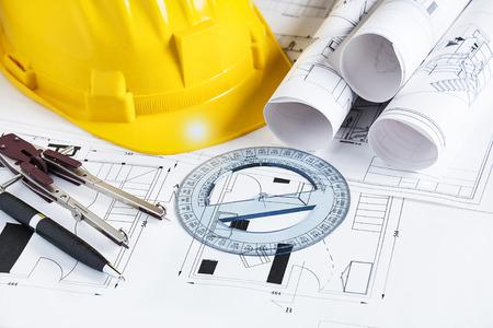 Foto de Engineer worplace with blueprints, compass, pen, protractor  and safety helmet - Imagen libre de derechos
