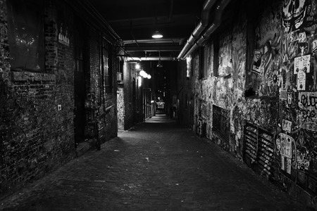 Black and white photo of darkness in a old grunge dirty street in the middle of night