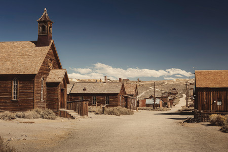 Colored vintage old looking photo of empty streets of abandoned ghost town Bodie in California, USA in the middle of a day.