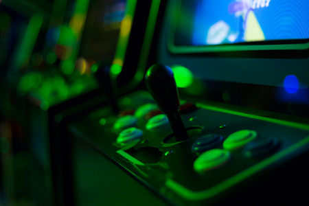 Photo pour Detail of a black joystick and buttons on an old arcade game in a gaming room with green lights - image libre de droit
