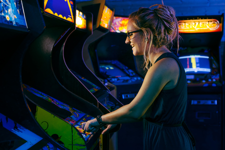Photo pour Smiling young female with blonde dreadlock hair and a blue dress is playing an old arcade video game in a dark gaming bar with various games in the background - image libre de droit