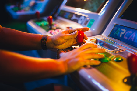 Photo pour Detail on Hands with Arcade Joystick Playing Old Arcade Video Game - image libre de droit