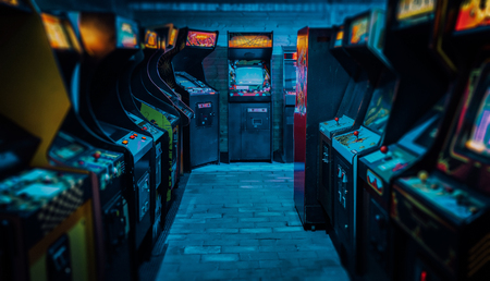 Photo for Old Vintage Arcade Video Games in an empty dark gaming room with blue light with glowing displays and beautiful retro design - Royalty Free Image