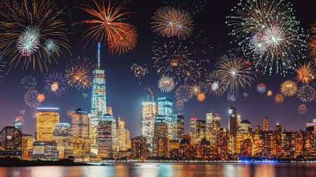 Foto de New Years Eve with colorful Fireworks over New York City skyline long exposure with dark blue-purple sky, orange city light glow and reflections in the river - Imagen libre de derechos