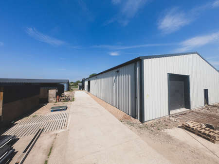 Foto de Wide angle view of the outside of a warehouse on a backdrop of blue sky. - Imagen libre de derechos