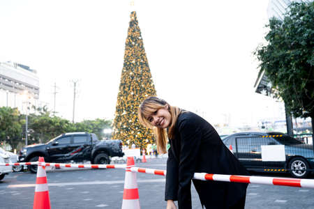 Photo pour Blond hair woman in black clothes bend down her upper body on the red and white fence at the parking lot with giant Christmas tree with light decoration. - image libre de droit