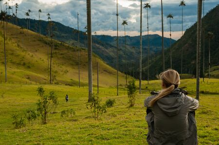 Girl with grey jacket sitting on green grass watching tall palm trees in Cocora Valley near Salento, Colombia
