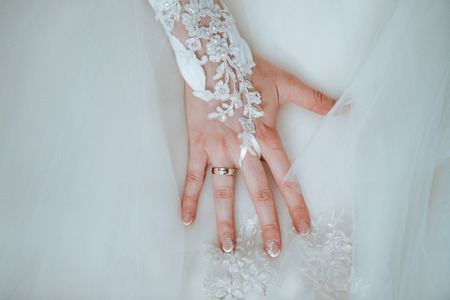 Foto de Bride's hand on her wedding dress with the ring and decorated nails - Imagen libre de derechos