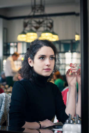Young woman smoking in a stylish old European cafe